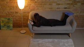 Muchacha caucásica joven con el pelo ondulado que miente en el sofá y que mira con la concentración en la tableta en atmósfera ca almacen de metraje de vídeo