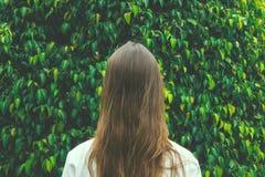 Muchacha caucásica joven de la mujer con el pelo largo de la castaña que se coloca con de nuevo al espectador en Forest Tree Foli Imagen de archivo libre de regalías