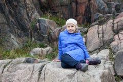 Muchacha caucásica joven en la chaqueta azul que se sienta en una roca Imagen de archivo