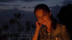 Muchacha caucásica joven que se sienta por el fuego en la naturaleza, y mirando la cámara, retrato metrajes