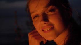 Muchacha caucásica joven que se sienta por el fuego en la naturaleza, y mirando la cámara, retrato almacen de video