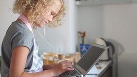 Muchacha caucásica linda que se sienta en la tabla y que usa el ordenador portátil, sonido que escucha en auriculares almacen de metraje de vídeo