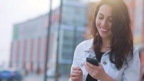 Muchacha caucásica morena atractiva que permanece en el sol delante de la alameda de compras y que usa su smartphone, mirando ade almacen de video