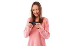 Muchacha caucásica positiva que juega con el teléfono mientras que se coloca sobre w Fotografía de archivo
