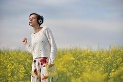 Muchacha caucásica que escucha la música con el auricular en el aire libre Fotografía de archivo