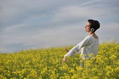 Muchacha caucásica que escucha la música con el auricular en el aire libre Fotos de archivo libres de regalías
