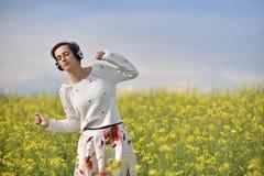 Muchacha caucásica que escucha la música con el auricular en el aire libre Fotos de archivo