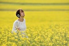 Muchacha caucásica que escucha la música con el auricular en el aire libre Imagenes de archivo