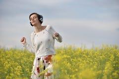 Muchacha caucásica que escucha la música con el auricular en el aire libre Fotografía de archivo libre de regalías