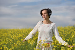 Muchacha caucásica que escucha la música con el auricular en el aire libre Imagen de archivo libre de regalías