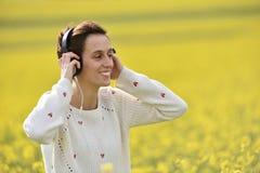 Muchacha caucásica que escucha la música con el auricular en el aire libre Foto de archivo libre de regalías