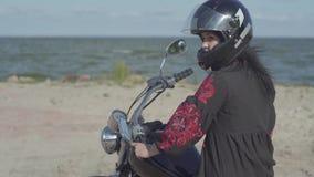 Muchacha caucásica que lleva el vestido negro y casco que se sienta en la motocicleta que mira en la cámara Afición, viajando y almacen de metraje de vídeo