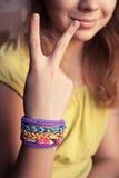 Muchacha caucásica que muestra dos fingeres con las pulseras de goma del telar Imágenes de archivo libres de regalías