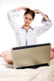 Muchacha caucásica que se sienta en su cama con su computadora portátil Imágenes de archivo libres de regalías