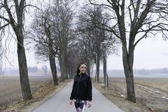 Muchacha caucásica sueca hermosa de la aptitud que se coloca al aire libre en callejón con los árboles Fotografía de archivo