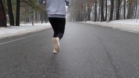 Muchacha cauc?sica atractiva joven que corre en el parque nevoso en invierno con los auriculares El cierre encima de la parte pos metrajes