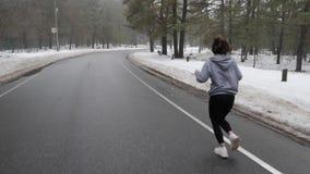 Muchacha cauc?sica atractiva joven que corre en el parque nevoso en invierno con los auriculares Detr?s siga el tiro metrajes