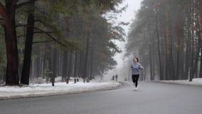 Muchacha cauc?sica atractiva joven que corre en el parque nevoso en invierno con los auriculares Front Static Shot metrajes
