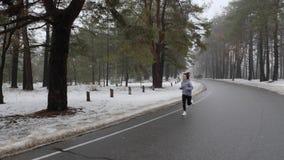 Muchacha cauc?sica atractiva joven que corre en el parque nevoso en invierno con los auriculares Front Static Shot C?mara lenta metrajes