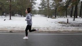 Muchacha cauc?sica atractiva joven que corre en el parque nevoso en invierno con los auriculares La parte delantera sigue el tiro metrajes