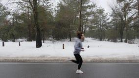 Muchacha cauc?sica atractiva joven que corre en el parque nevoso en invierno con los auriculares Tiro lateral metrajes