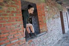 Muchacha cerca de la pared de ladrillo en estilo militar fotos de archivo libres de regalías