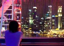 Muchacha cerca de la ventana y de la vista de la ciudad lluviosa por completo de luces Imagen de archivo libre de regalías