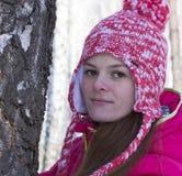 Muchacha cerca de un árbol de abedul en bosque del invierno Imagen de archivo