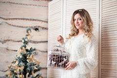 Muchacha cerca del árbol de navidad adornado en interior ligero hermoso Foto de archivo libre de regalías