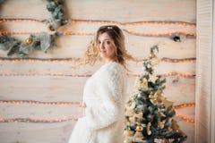 Muchacha cerca del árbol de navidad adornado en interior ligero hermoso Imagen de archivo libre de regalías