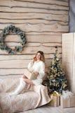 Muchacha cerca del árbol de navidad adornado en interior ligero hermoso Fotos de archivo libres de regalías