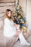 Muchacha cerca del árbol de navidad adornado en interior ligero hermoso Foto de archivo