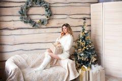 Muchacha cerca del árbol de navidad adornado en interior ligero hermoso Imagen de archivo
