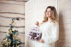 Muchacha cerca del árbol de navidad adornado en interior ligero hermoso Fotos de archivo
