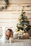 Muchacha cerca del árbol de navidad adornado en interior ligero hermoso Imágenes de archivo libres de regalías