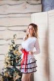 Muchacha cerca del árbol de navidad adornado en interior ligero hermoso Imagenes de archivo
