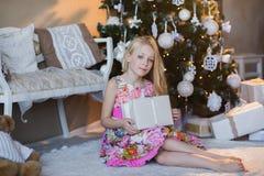 Muchacha cerca del árbol de navidad con los presentes y los juguetes, cajas, la Navidad, Año Nuevo, forma de vida, día de fiesta, Fotografía de archivo