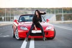 Muchacha cerca del coche rojo Fotografía de archivo