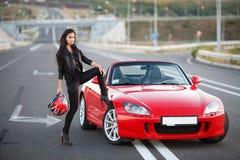 Muchacha cerca del coche rojo Fotos de archivo libres de regalías