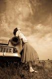 Muchacha cerca del coche viejo, foto en estilo amarillo de la vendimia Imagen de archivo libre de regalías