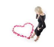 Muchacha cerca del corazón hecho de pétalos color de rosa fotografía de archivo libre de regalías
