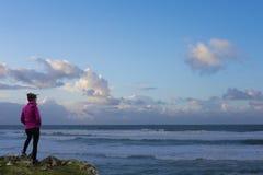 Muchacha cerca del mar en la puesta del sol Imagenes de archivo