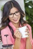 Muchacha china asiática de la mujer en café de consumición de la cocina Imagenes de archivo