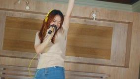 Muchacha china asiática loca y feliz del estudiante que canta la canción en línea del Karaoke con el micrófono y el teléfono móvi almacen de video