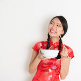 Muchacha china asiática que come y que mira para arriba Imagenes de archivo