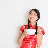 Muchacha china asiática que come y que piensa Imagen de archivo libre de regalías