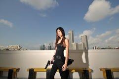 Muchacha china asiática que lleva una pistola 2 imagen de archivo libre de regalías