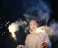 Muchacha china asiática que sostiene el fuego artificial de la bengala con la mano en el fondo negro Morenita, mirando Imágenes de archivo libres de regalías