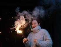 Muchacha china asiática que sostiene el fuego artificial de la bengala con la mano en el fondo negro Morenita, mirando Fotografía de archivo