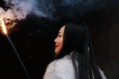 Muchacha china asiática que sostiene el fuego artificial de la bengala con la mano en el fondo negro Morenita, mirando Foto de archivo